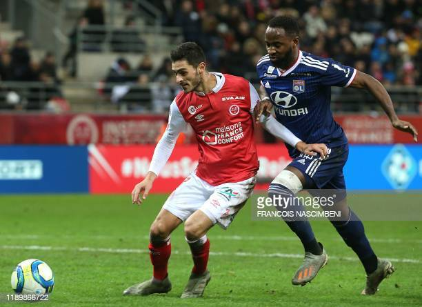 Reims' French midfielder Xavier Chavalerin fights for the ball with Lyon's French forward Moussa Dembele during the French L1 football match between...