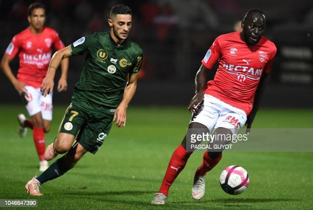 Reims' French midfielder Xavier Chavalerin vies with Nîmes' French forward Sada Thioub during the French L1 football match between Nîmes and Reims on...