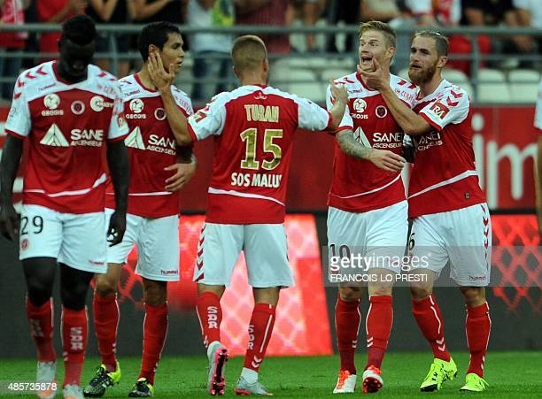 Reims' Gaëtan Charbonnier is congratulated by teammates after scoring a goal during the French L1 football match between Reims and Lorient on August...