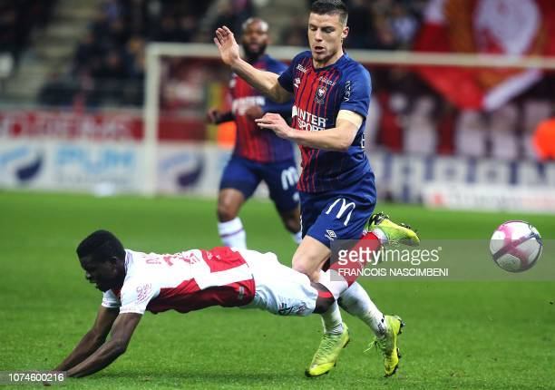 Reims' Malian midfielder Moussa Doumbia vies for the ball with Caen's French defender Frederic Guilbert during the French L1 football match between...