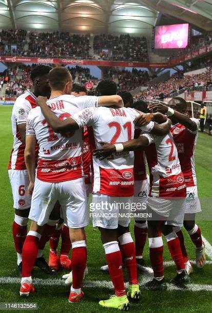 Reims' players celebrate after defender Abdul Rahman Baba scored a goal during the French Ligue 1 football match between Reims and Paris SaintGermain...