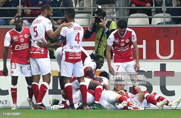 Reims' players celebrate after French Midfielder Mathieu Cafaro scored a goal during the French Ligue 1 football match between Reims and Paris...