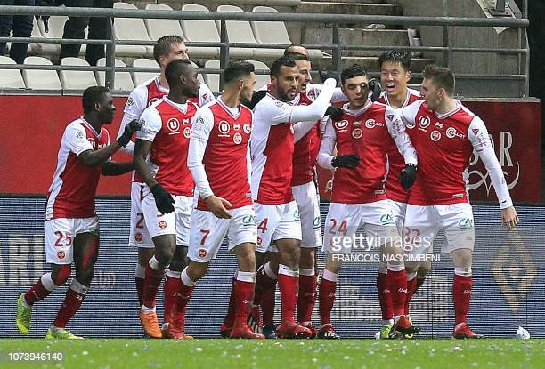 Reims' players celebrate after Reims' French midfielder Mathieu Cafaro scored during the French L1 football match between Stade de Reims and Racing...