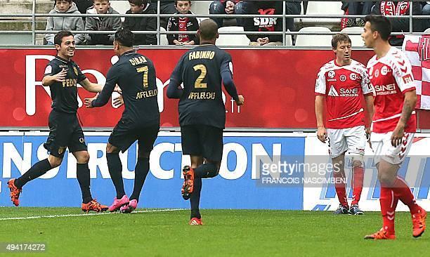 Reims' players react as Monaco's Portuguese midfielder Silva Bernardo celebrates with teammates after scoring a goal during the French Ligue 1...