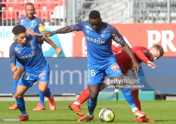 Reims' Senegalese midfielder Dion Lopy challenges Brest's French midfielder Hugo Magnetti , during the French L1 football match between Stade...