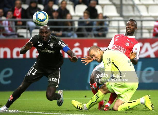 Reims' Serbian goalkeeper Predrag Rajkovic vies with Dijon's forward Julio Tavares during the French L1 football match between Reims and Dijon on...