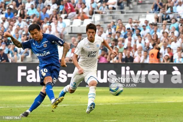 Reims' South Korean forward Hyun-jun Suk shoots and scores a goal next to Marseille's Japanese defender Hiroki Sakai during the French L1 football...