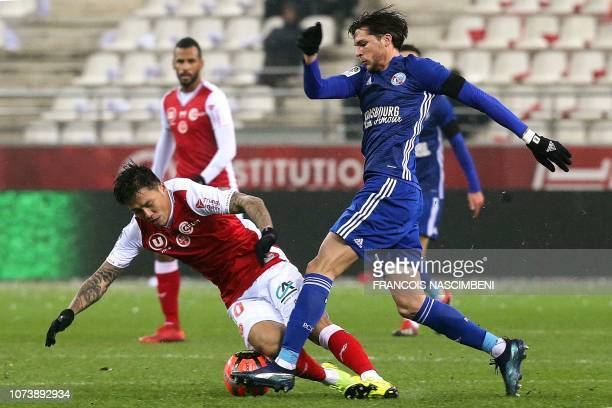Reims' South Korean forward Hyunjun Suk vies for the ball with Strasbourg's French midfielder Jonas Martin during the French L1 football match...
