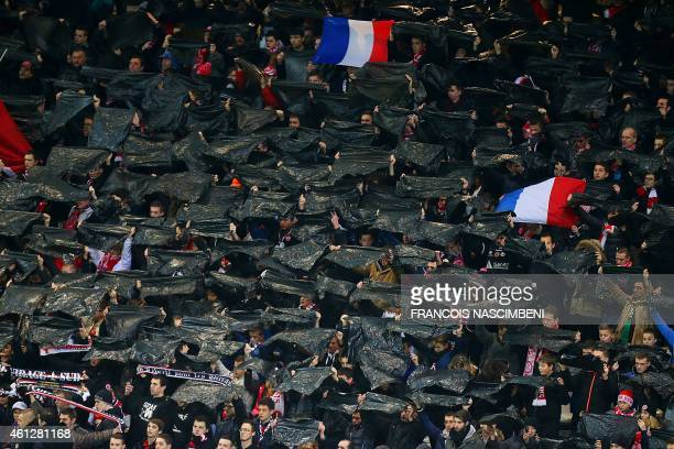 Reims' supporters hold blask flags in tribute to the victims of three days of terror and twin siege dramas that claimed 17 victims including the...