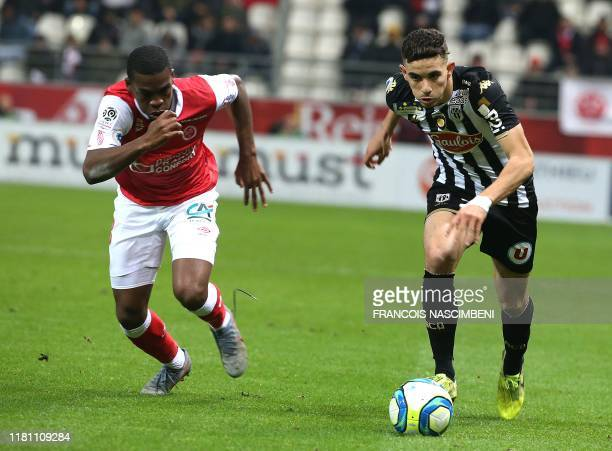 Reims' Swiss midfielder Dereck Kutesa vies with Angers' French defender Rayan Ait-Nouri during the French L1 football match Reims vs Angers on...