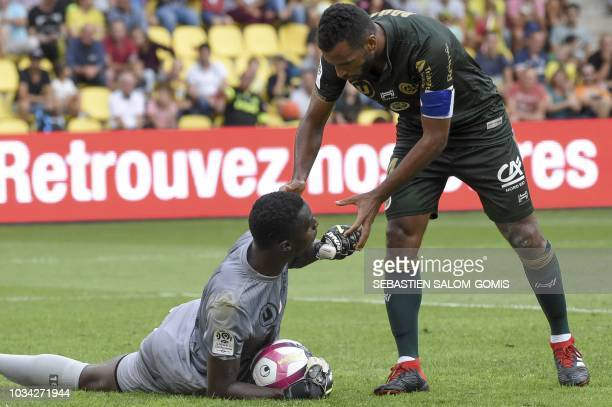 Reims' Togolese midfielder Alexis Romao congratulates Reims' French goalkeeper Edouard Mendy during the French L1 football match between Nantes and...