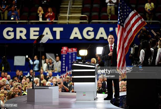 Reince Priebus chairman of the Republican National Committee takes part in the national anthem on stage before the start of the first day of the...