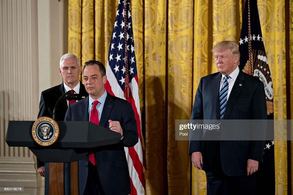 Reince Priebus, White House chief of staff, speaks as U.S. President Donald Trump and U.S. Vice President Mike Pence listen during a swearing in ceremony of White House senior staff in the East Room of the White House on January 22, 2017 in Washington, DC. Trump today mocked protesters who gathered for large demonstrations across the U.S. and the world on Saturday to signal discontent with his leadership, but later offered a more conciliatory tone, saying he recognized such marches as a 'hallmark of our democracy.'