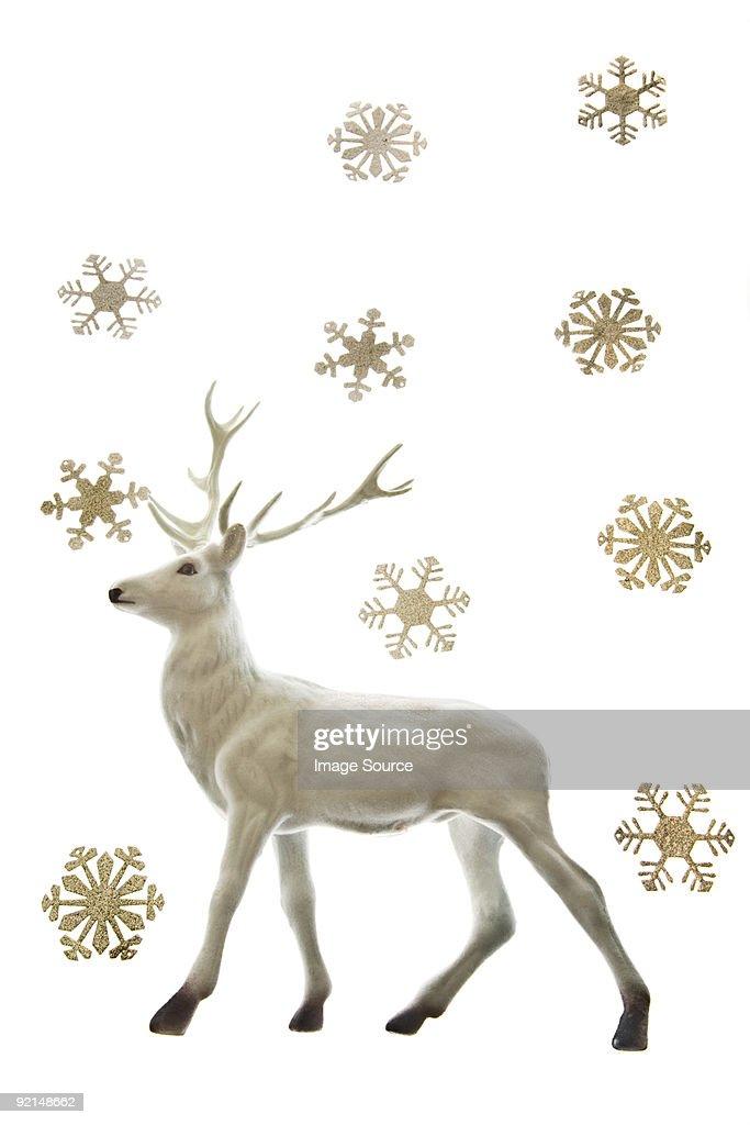 Reindeer figurine and snowflakes : Stock Photo