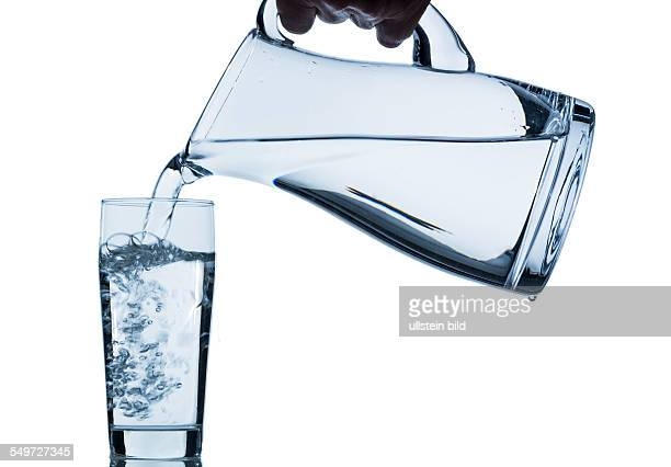Reines Wasser wird in ein Wasserglas aus einem Krug eingeleert Frisches Trinkwasser
