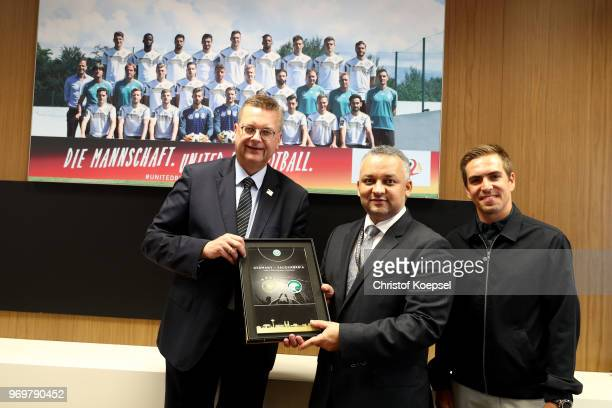 Reinhard Grindel DFB president and Philipp Lahm amabassador of 'United for Football' application for Euro 2024 hand out a present to Adel Ezzat...