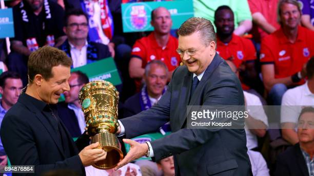 Reinhard Grindel DFB president carries tghe DFB cup and hands out to Alexander Bommes ARD moderator during the DFB Cup Draw at Deutsches...