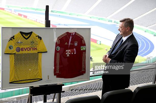 Reinhard Grindel president of Deutsche Fussball Bund DFB is seen with former jerseys of Borussia Dortmund and Bayern Muenchen for the Hallway of Fame...
