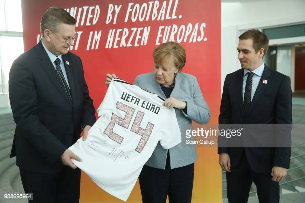 Reinhard Grindel President of the German Football Federation German Chancellor Angela Merkel and retired German football star Philipp Lahm look at a...