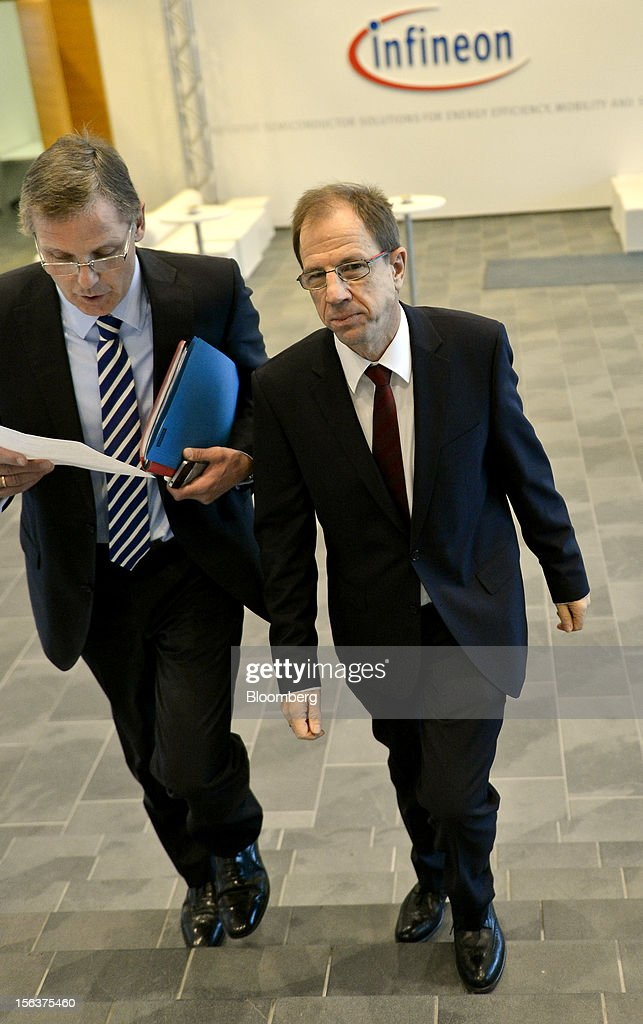 Reinhard Ploss, chief executive officer of Infineon Technologies AG, right, makes his way to the company's earnings news conference in Munich, Germany, on Wednesday, Nov. 14, 2012. Infineon Technologies AG, Europe's second-biggest semiconductor maker, reported fourth-quarter revenue that declined less than analysts expected and forecast sales to drop next year. Photographer: Guenter Schiffmann/Bloomberg via Getty Images