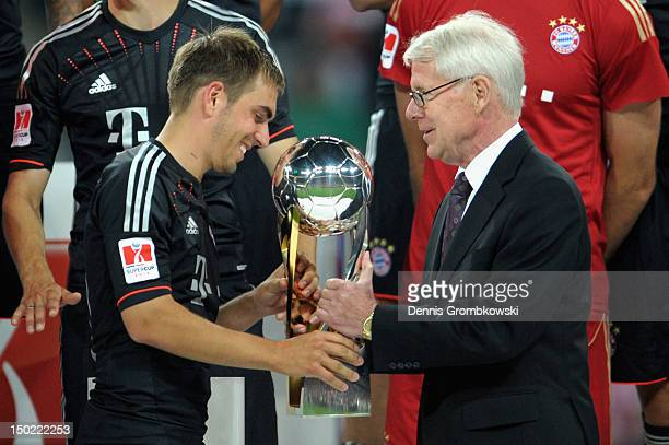 Reinhard Rauball president of the German Football League DFL hands over the trophy to Philipp Lahm of Bayern after the Bundesliga Supercup 2012 match...
