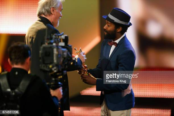 Reinhold Vorschneider receives the Award for Best Cinematography from actor Eric Kabongo at the Lola German Film Award show at Messe Berlin on April...