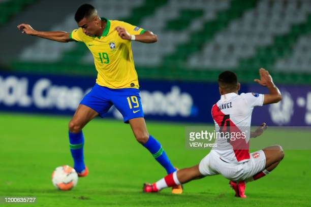 Reinier of Brazil fights for the ball against Gianfranco Chavez of Peru during their CONMEBOL PreOlympic soccer game at Centenario Stadium on January...