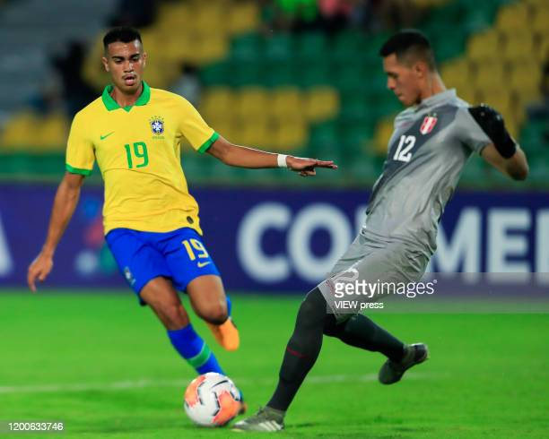 Reinier of Brazil fights for the ball against goalkeeper Renato Solis of Peru during their CONMEBOL PreOlympic soccer game at Centenario Stadium on...