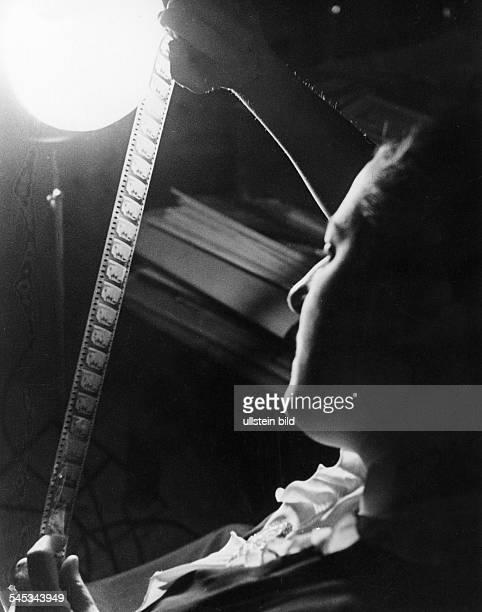 Reiniger, Lotte - Filmmaker, Germany *02.06.1899-+ Animation pioneer - portrait, looking at a filmstrip - 1935 - Photographer: Wolf Strache - Vintage...