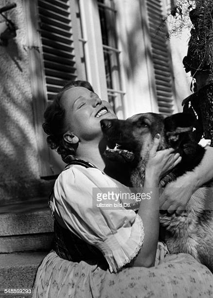 Reining Maria Singer Soprano Austria * with her dog on the stairs of her country house in Geiselgasteig near Munich 1941 Photographer Hedda Walther...