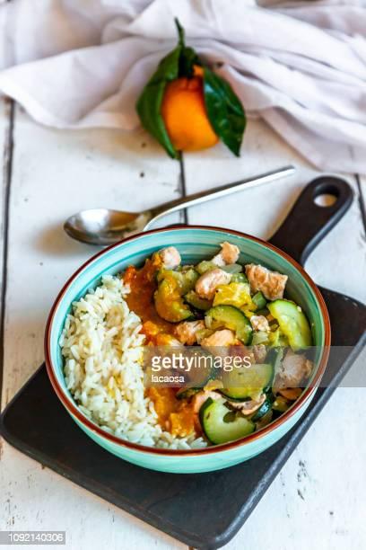 Reis mit Lachs, Zucchini, Mandarine und Kokoscurrysauce in einer Schüssel