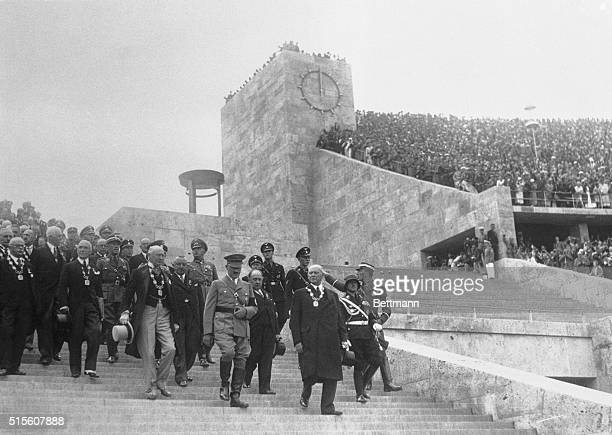Reischfuhrer Adolf Hitler is shown leading Olympic officials into the Olympic Stadium at Berlin for the inauguration of the 1936 games On the right...