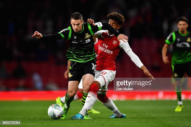 Reiss Nelson of Arsenal and Tommy Rowe of Doncaster Rovers battle for possession during the Carabao Cup Third Round match between Arsenal and...