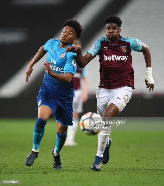 Reiss Nelson of Arsenal takes on Ben Johnson of West Ham during the match between West Ham United and Arsenal at London Stadium on April 20 2018 in...