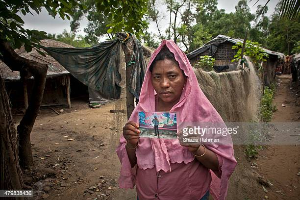 Rekha Begum holds a photo of her son Shomshed Alam July 4 2015 in Shamlapur Bangladesh Alam and his family came to Bangladesh 12 years ago after...