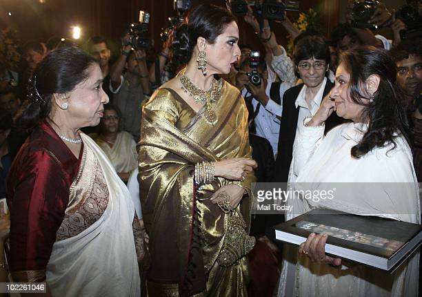 Rekha chats up with Jaya Bachchan as Asha Bhonsle looks on at the launch of Chehere a coffee table book compiled by celebrity photographer Gautam...