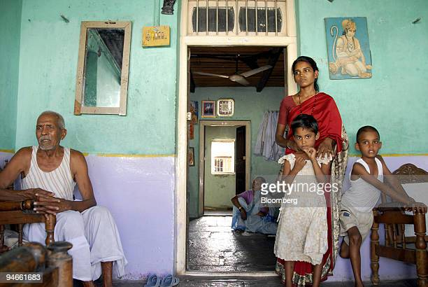 Rekha Gurnule standing in red sari widow of farmer Chandrakant Gurnule who had loans of 150000 rupees when he committed suicide is seen with daughter...