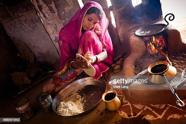 Rekha is preparing chapatis with a tawa on fire in her traditional kitchen a hut in a small Bishnoi village located in Rajasthan India