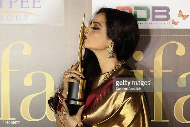 Rekha kisses her trophy after she wins the Lifetime Achievement award at the 2012 International India Film Academy Awards at the Singapore Indoor...