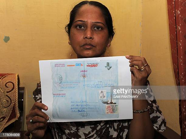 Rekha Nanakchand Yadav poses with a photocopy of a letter she claims was sent by her brother Kuldeep Kumar Yadav who is currently being held in...