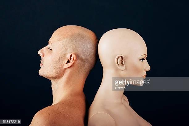 Relationship concept with bald caucasian man against female bald mannequin