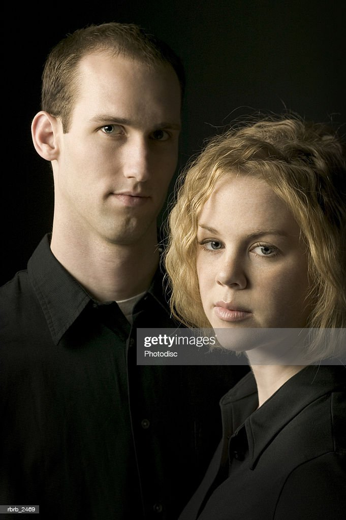 relationship portrait of a young couple dressed in black as they look around : Foto de stock