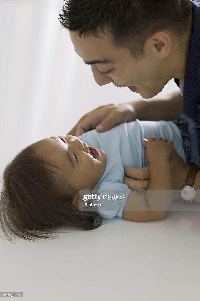 relationship portrait of a young father as he leans over and plays with his toddler daughter : Foto de stock