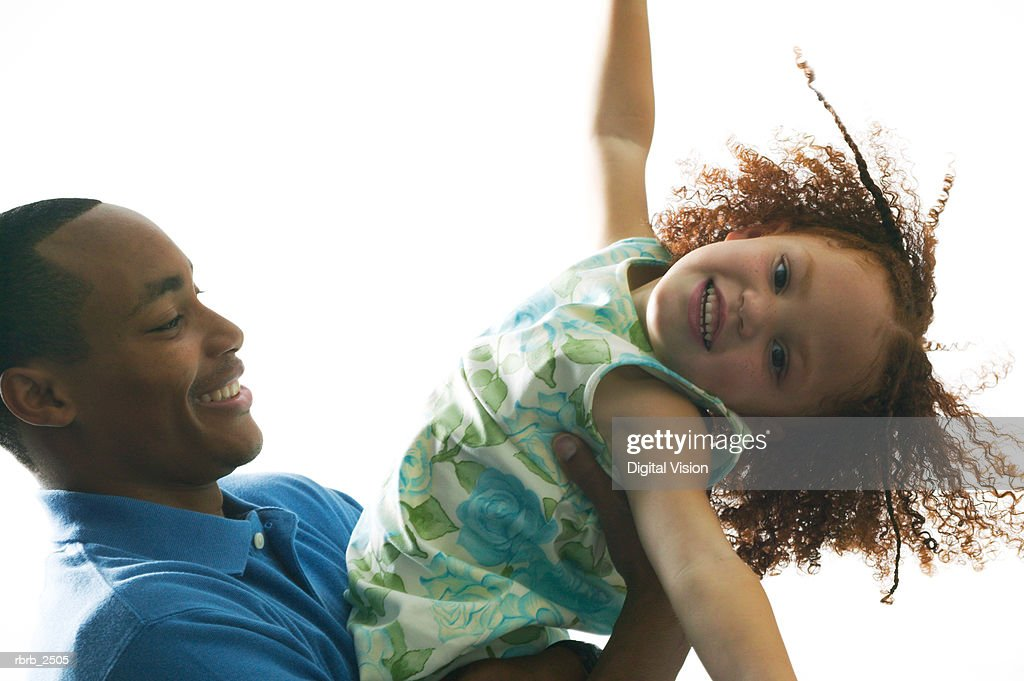 relationship portrait of an adult father as he holds and plays with his young daughter : Foto de stock