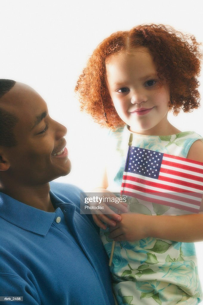 relationship portrait of an adult father as he holds his young daughter with an american flag : Foto de stock