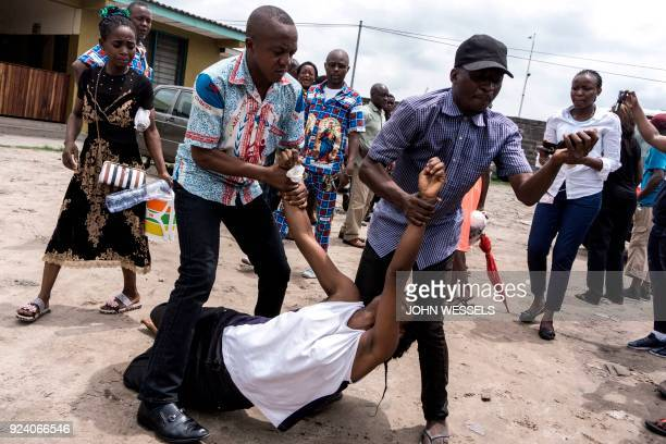 A relative carried by two men reacts and mourns the death of a man who succumbed to a gun shot wound during a protest called on by the Catholic...