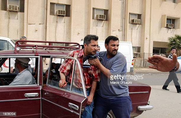 A relative carries a wounded Iraqi to North Baghdad's alKindi Hospital April 13 2003 Baghdad Iraq Widespread looting continues all over the capital...