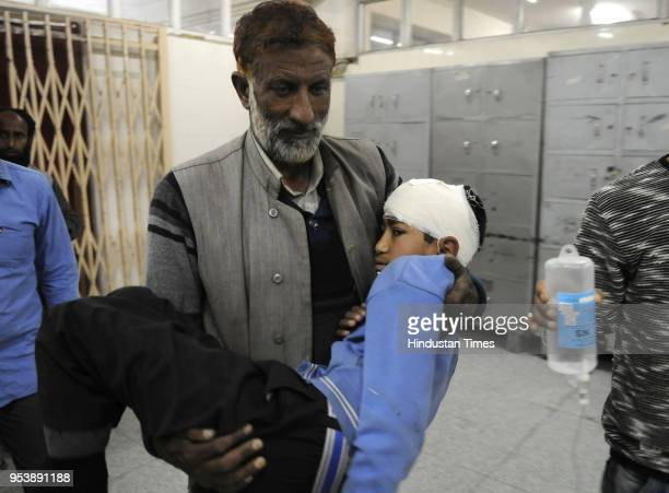 A relative carries injured minor student in SMHS hospital after a private school bus was attacked by stonepelters in Zavoora area on May 2 2018 of...