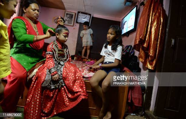 A relative combs the hairs of Nepal's Living Goddess also called the 'Kumari' at her house in Patan in the outskirts of Kathmandu on June 9 2019 The...