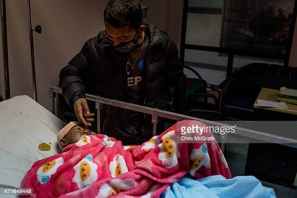 A relative comforts nine year old Sunmaya Tamang as she recovers from brain surgery for a fractured skull at the National Trauma center on April 30...